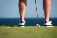 Golfboll och pinnen med golfaren lägger benen på ryggen i förgrunden Royaltyfri Fotografi