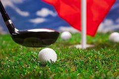 Golfboll och slagträ på gräs! Arkivbilder
