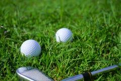 Golfboll och utslagsplats på grön kursbakgrund för golf arkivfoto