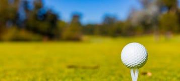 Golfboll på en utslagsplats på en golfbana royaltyfria bilder