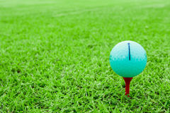 Golfboll på en utslagsplats i kurs för grönt gräs royaltyfri fotografi