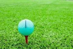 Golfboll på en utslagsplats i kurs för grönt gräs arkivfoto