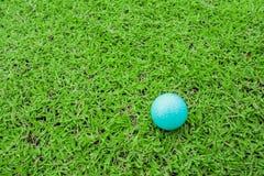 Golfboll på en utslagsplats i kurs för grönt gräs arkivfoton