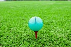 Golfboll på en utslagsplats i kurs för grönt gräs fotografering för bildbyråer