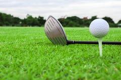 Golfboll på en utslagsplats och chauffören i grönt gräs jagar royaltyfria foton