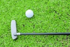 Golfboll på en utslagsplats och puttern i grönt gräs jagar arkivbilder