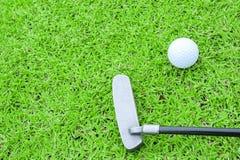 Golfboll på en utslagsplats och puttern i grönt gräs jagar arkivbild