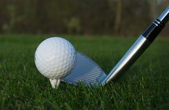 Golfboll på en vit utslagsplats Fotografering för Bildbyråer