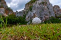 Golfboll på gräs nära berget royaltyfria bilder