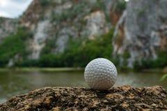 Golfboll på gräs nära den lilla sjön royaltyfri bild