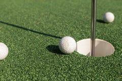 Golfboll på hålet royaltyfri bild