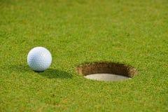 Golfboll på kanten av koppen Arkivfoton
