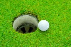 Golfboll på kanten av koppen, golfboll och golfhål på grönt gräs royaltyfria foton