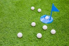 Golfboll på med en i hål på gräs royaltyfri fotografi