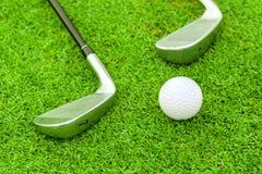 Golfboll på utslagsplats framme av chaufförgräsplankursen royaltyfria bilder