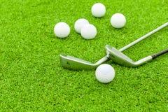 Golfboll på utslagsplats framme av chaufförgräsplankursen royaltyfri bild
