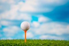Golfboll på utslagsplats på gräs på bakgrund för blå himmel och moln royaltyfri bild
