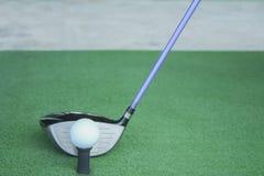 Golfboll på utslagsplats med chaufförklubban som är främst av chauffören som kör r royaltyfri fotografi