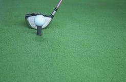 Golfboll på utslagsplats med chaufförklubban som är främst av chauffören som kör r royaltyfri foto