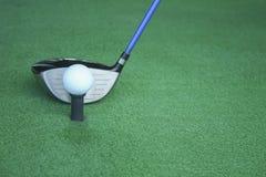 Golfboll på utslagsplats med chaufförklubban som är främst av chauffören som kör r royaltyfri bild