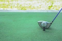 Golfboll på utslagsplats med chaufförklubban som är främst av chauffören som kör r arkivfoton
