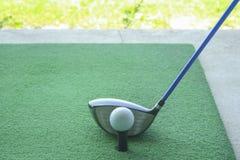 Golfboll på utslagsplats med chaufförklubban som är främst av chauffören som kör r arkivfoto