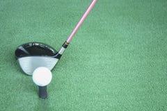 Golfboll på utslagsplats med chaufförklubban som är främst av chauffören som kör r royaltyfria foton