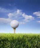 Golfboll på utslagsplats med gräs, den blåa skyen och oklarheter Royaltyfria Foton