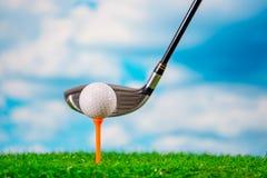 Golfboll på utslagsplats och golfklubb på gräs på bakgrund för blå himmel och moln arkivfoto