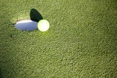 Golfboll som sätter på kanten av ett hål arkivbilder