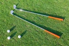 Golfbollar och golfklubbar på gräs arkivbilder