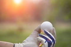 Golfbollar och utslagsplats i händerna arkivfoto