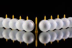 Golfbollar på det svarta glass skrivbordet Arkivbilder