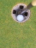 Golfbollen spela golfboll i hål in Arkivbild