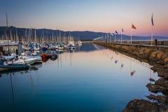 Golfbreker en boten bij de haven bij zonsondergang, in Santa Barbara, stock afbeeldingen