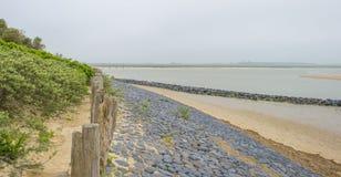 Golfbreker op een recreatief strand in de lente die land beschermen tegen overzees stock foto's