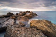 Golfbreker van rotsen bij zonsopgang stock fotografie