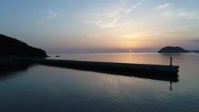 Golfbreker van steen in het zonsondergangoverzees stock videobeelden