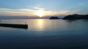 Golfbreker van steen in het zonsondergangoverzees stock footage