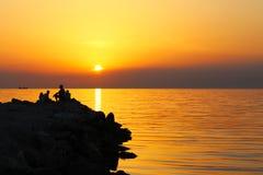 Golfbreker in zonsondergang met silouette van golfbreker stock foto