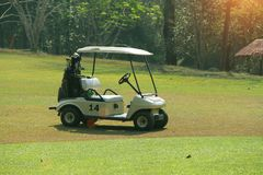 Golfcar in beautiful golf course in the evening golf course with. Sunshine in thailand Royalty Free Stock Photos