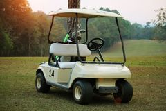 Golfcar in beautiful golf course in the evening golf course with. Sunshine in thailand Stock Photos