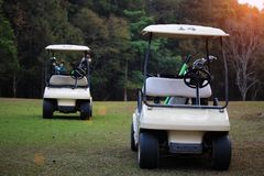 Golfcar in beautiful golf course in the evening golf course with. Sunshine in thailand Stock Images