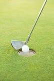 Golfclub, der Ball am Loch setzt Stockfotografie