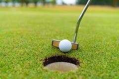 Golfclub en bal in gras, Golfclub en golfbal dichte omhooggaand op grasgebied met zonsondergang stock afbeelding