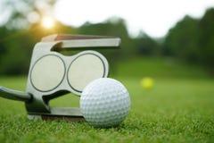 Golfclub und Golfball nah oben in der Rasenfläche mit Sonnenuntergang stockfotos
