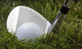 Golfclub und Kugel im Gras Stockfotos