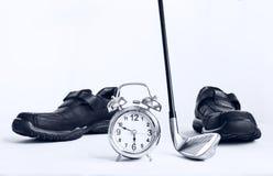 Golfclub und Wecker mit Geschäftslederschuhen, Konzept O Stockbilder