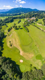 Golfcourse Bavaria Mountains. This is the beautiful Golfcourse close to Bad Tölz Bavaria Germany. This shot was made with a drone out of the sky. Wonderful royalty free stock photography