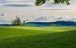 Golfcourse putting green. Idyllic golfcourse with putting green in front royalty free stock photography